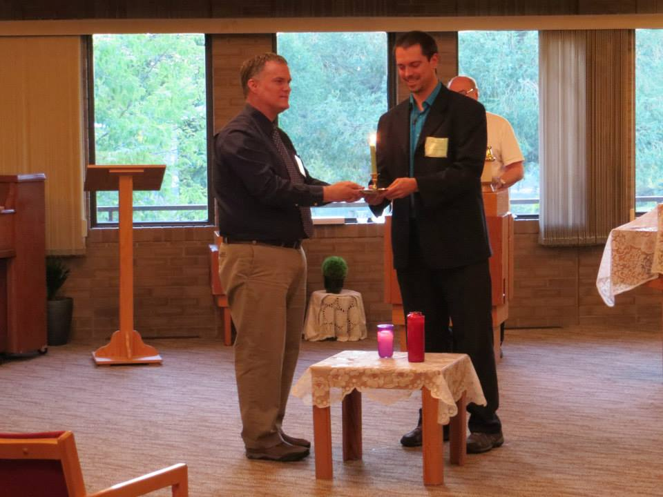 Darren Dahl and Norman Levesque passing the candle from the Prairie Centre for Ecumenism to the Canadian Centre for Ecumenism, hosts of the 2018 Forum on Inter-Church Dialogues. Photo by André Lavergne, ELCIC